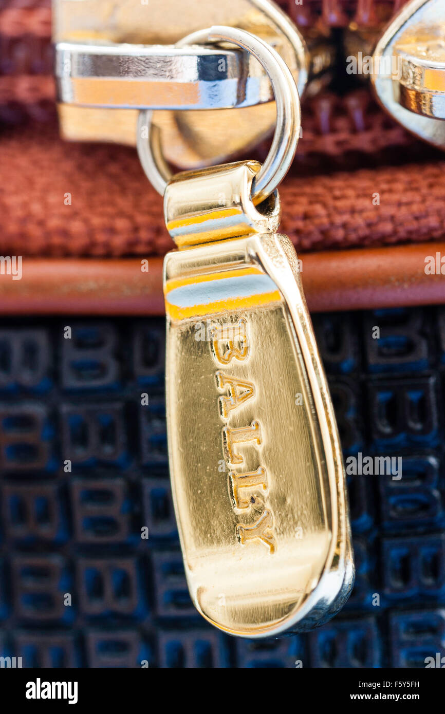 Close up of zipper heads on Bally fashionable bag. Gold coloured zippers with 'bally' brand name on finger - Stock Image
