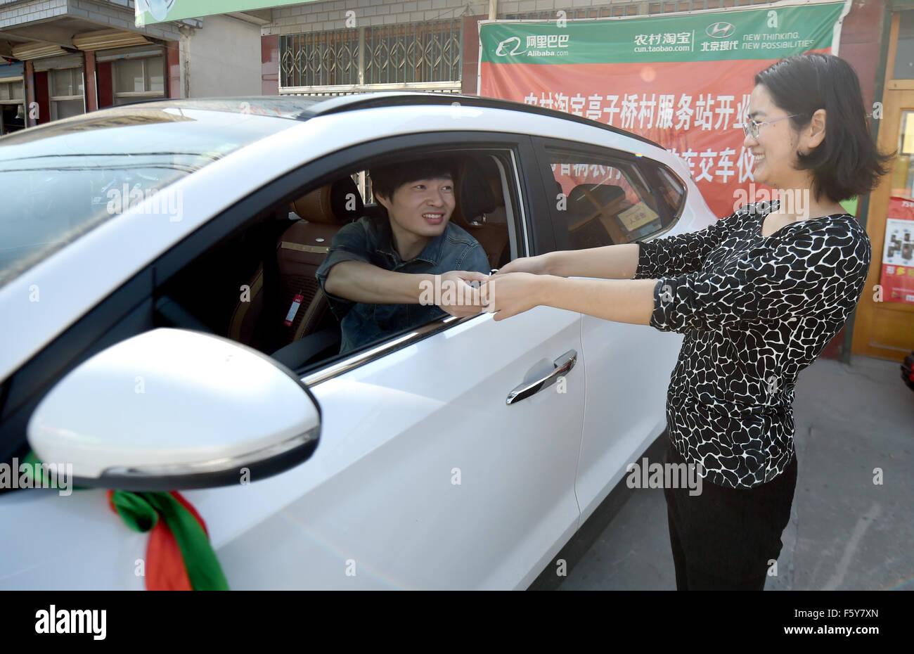 (151110) -- HANGZHOU, Nov. 10, 2015 (Xinhua) -- Chen Tao(L), a 'cuntao partner', delivers a car that a villager - Stock Image