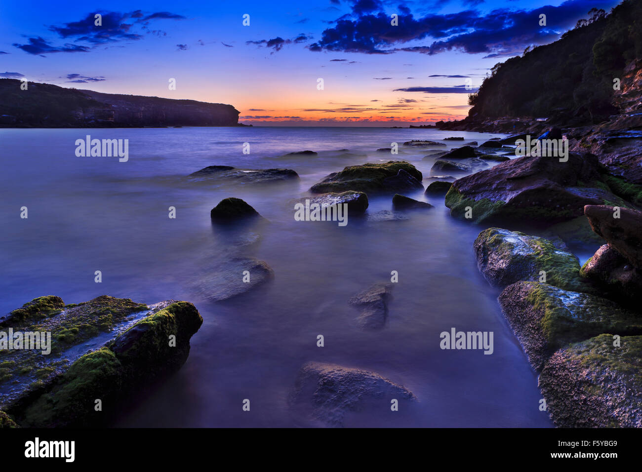 Coastal rocky beach in lagoon of Pacific coast in Australia near Sydney's Royal National Park at sunrise during - Stock Image
