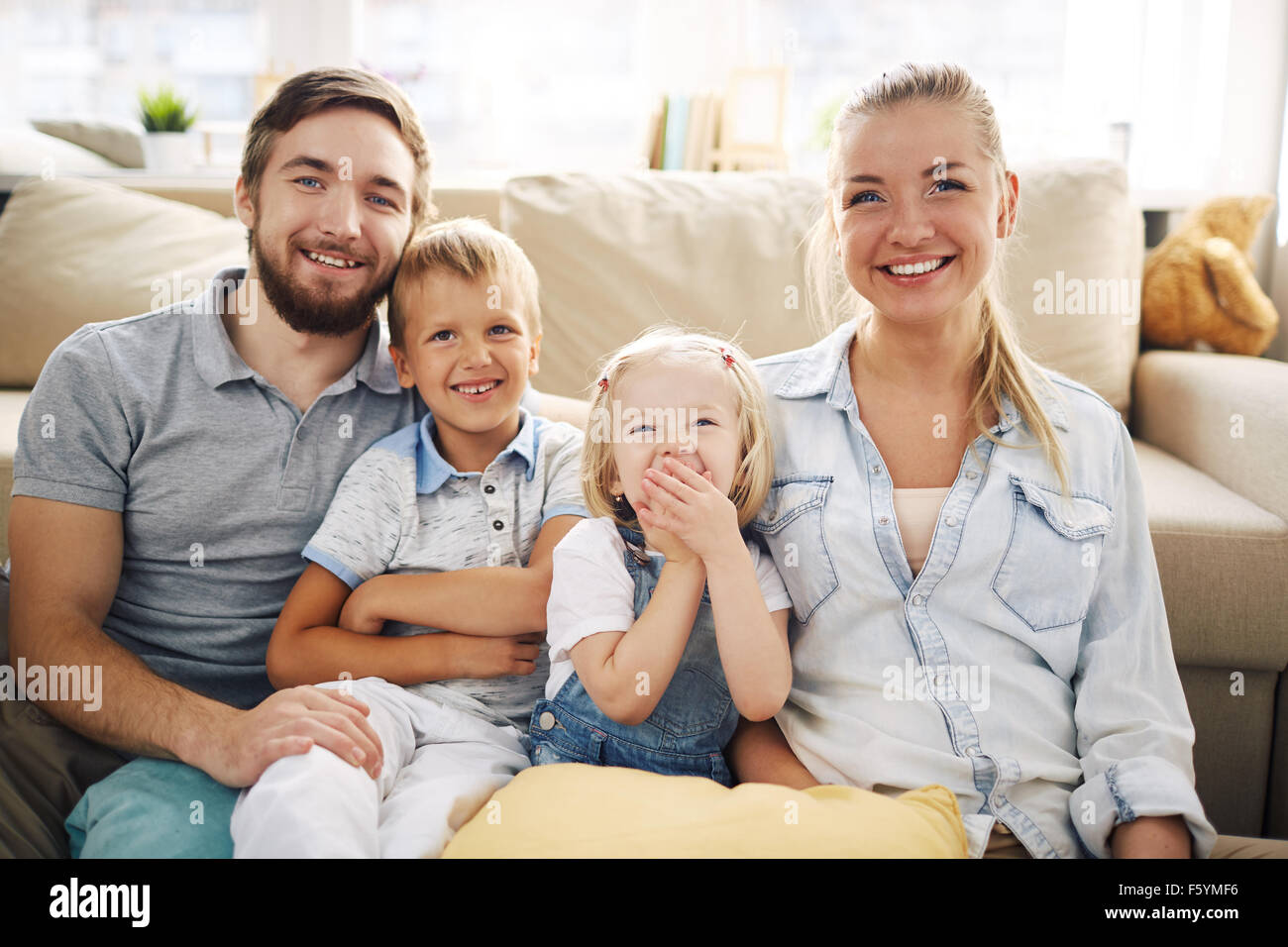 Happy family in casualwear relaxing at home - Stock Image