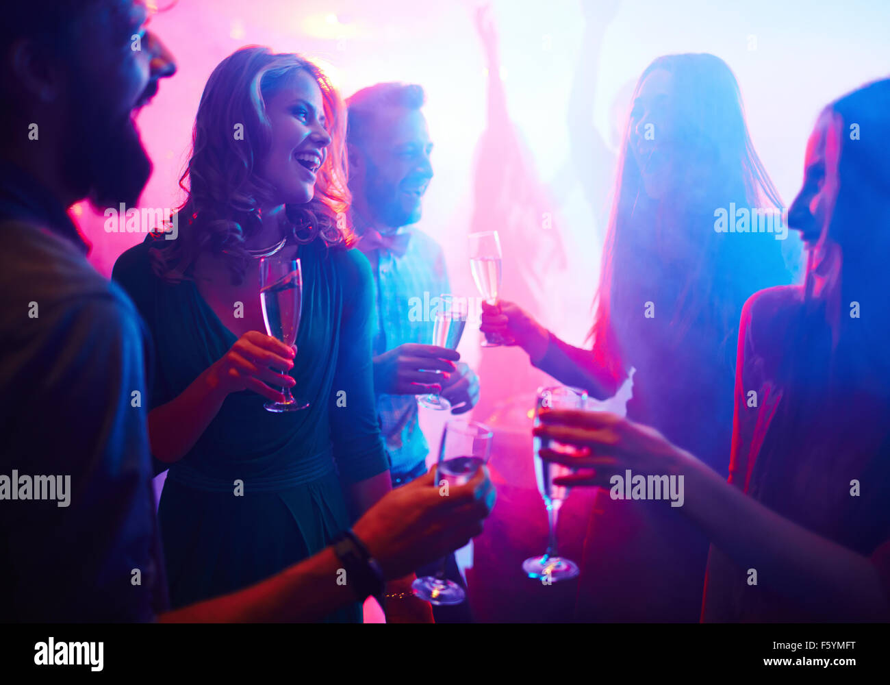 Cheerful friends with champagne spending time in night club - Stock Image