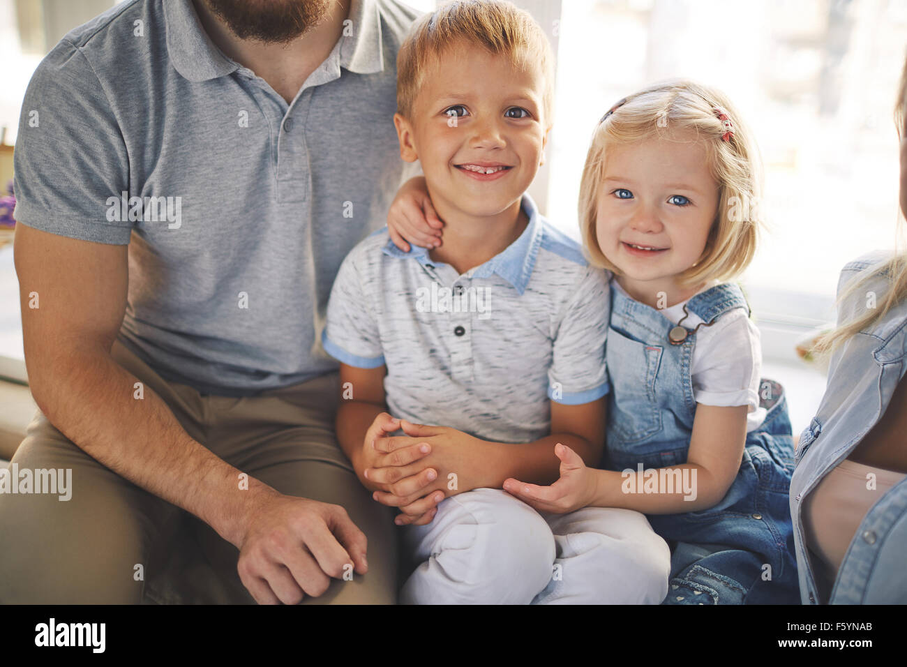Adorable siblings looking at camera with smiles - Stock Image