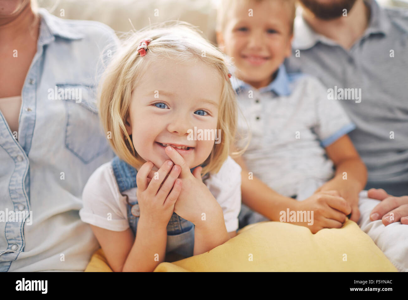 Sweet little girl looking at camera with her parents and brother near by Stock Photo