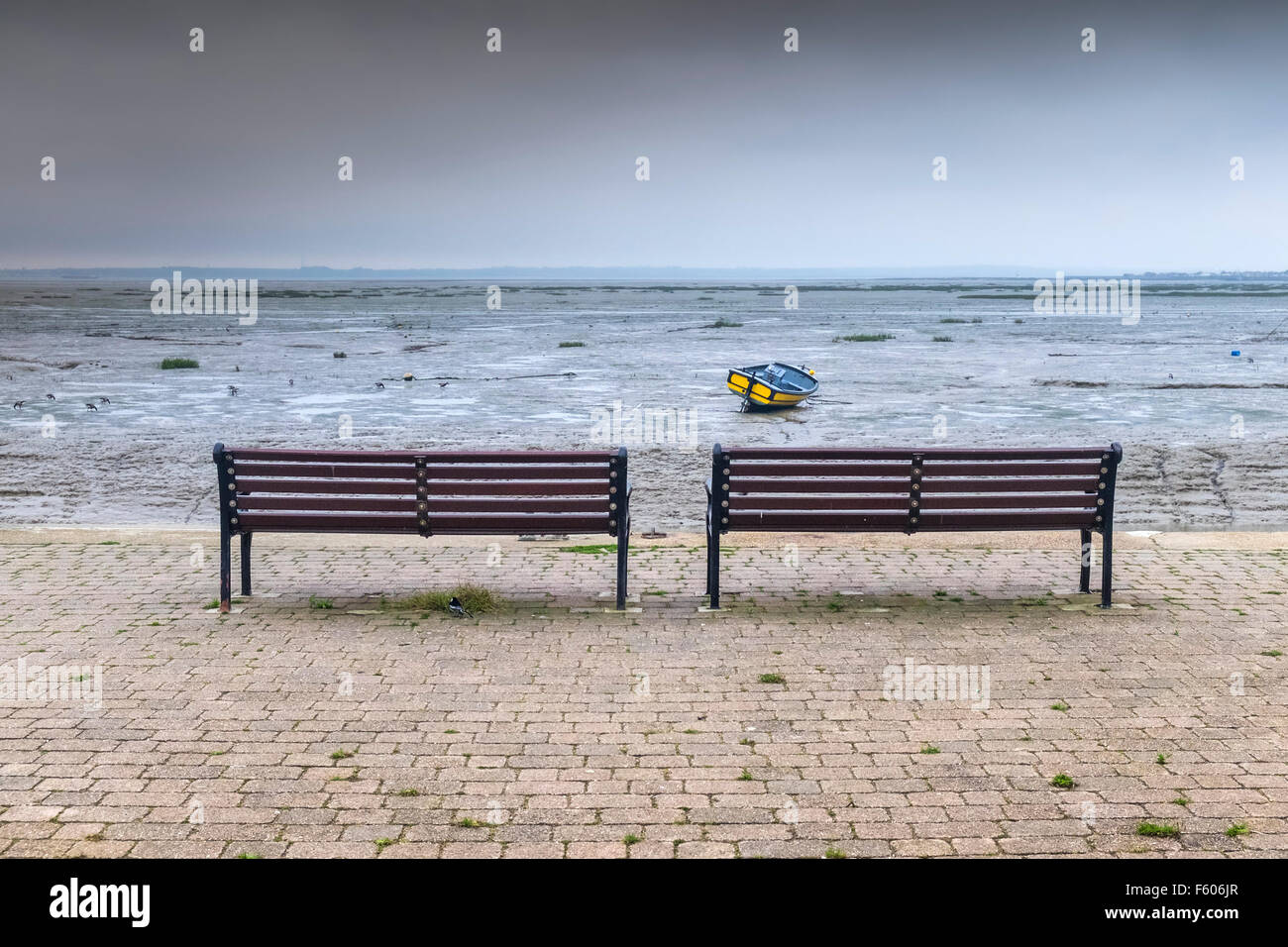 Two benches on a wharf overlooking the Thames Estuary in Essex. - Stock Image