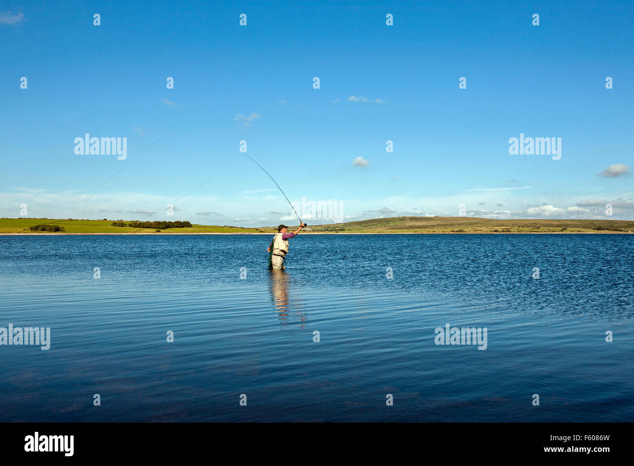 fly fishing on Colliford reservoir lake Bodmin Moor Cornwall lone man casting with rod on still lake blue sky - Stock Image
