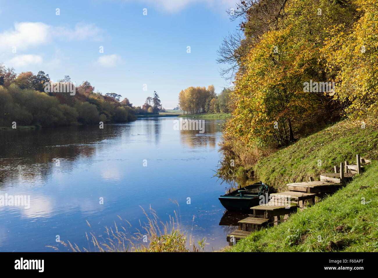 View along River Tweed valley with moored boat by steps in autumn. Kelso, Berwickshire, Scottish Borders, Scotland, - Stock Image