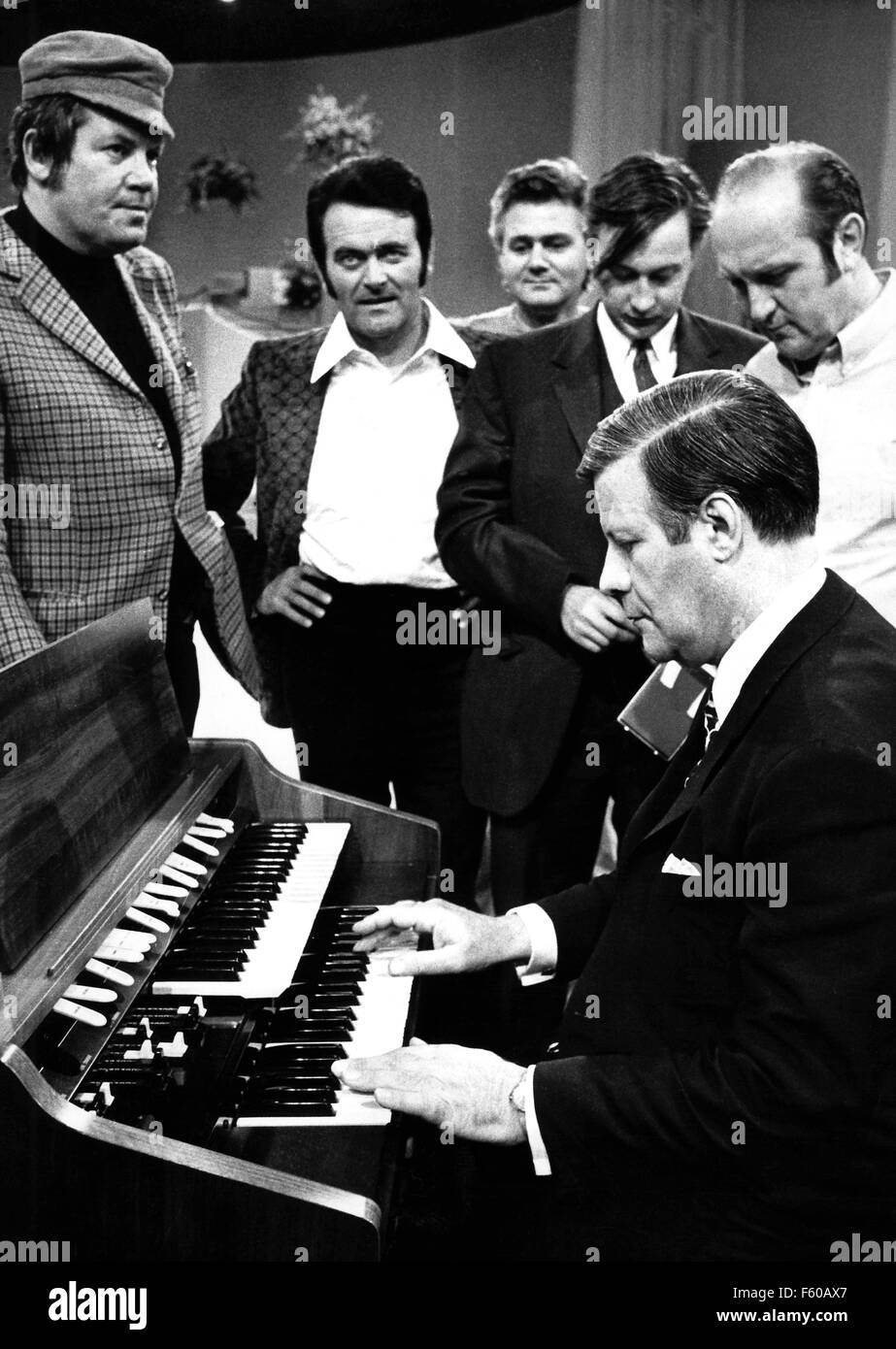 Helmut Schmidt plays organ on 6 July 1972 at the ZDF studio in Wiesbaden. Wim Thoelke (L) and Max Greger (2nd from left) are watching him. On 23 December 2003, Schmidt becomes 85 years old. Stock Photo