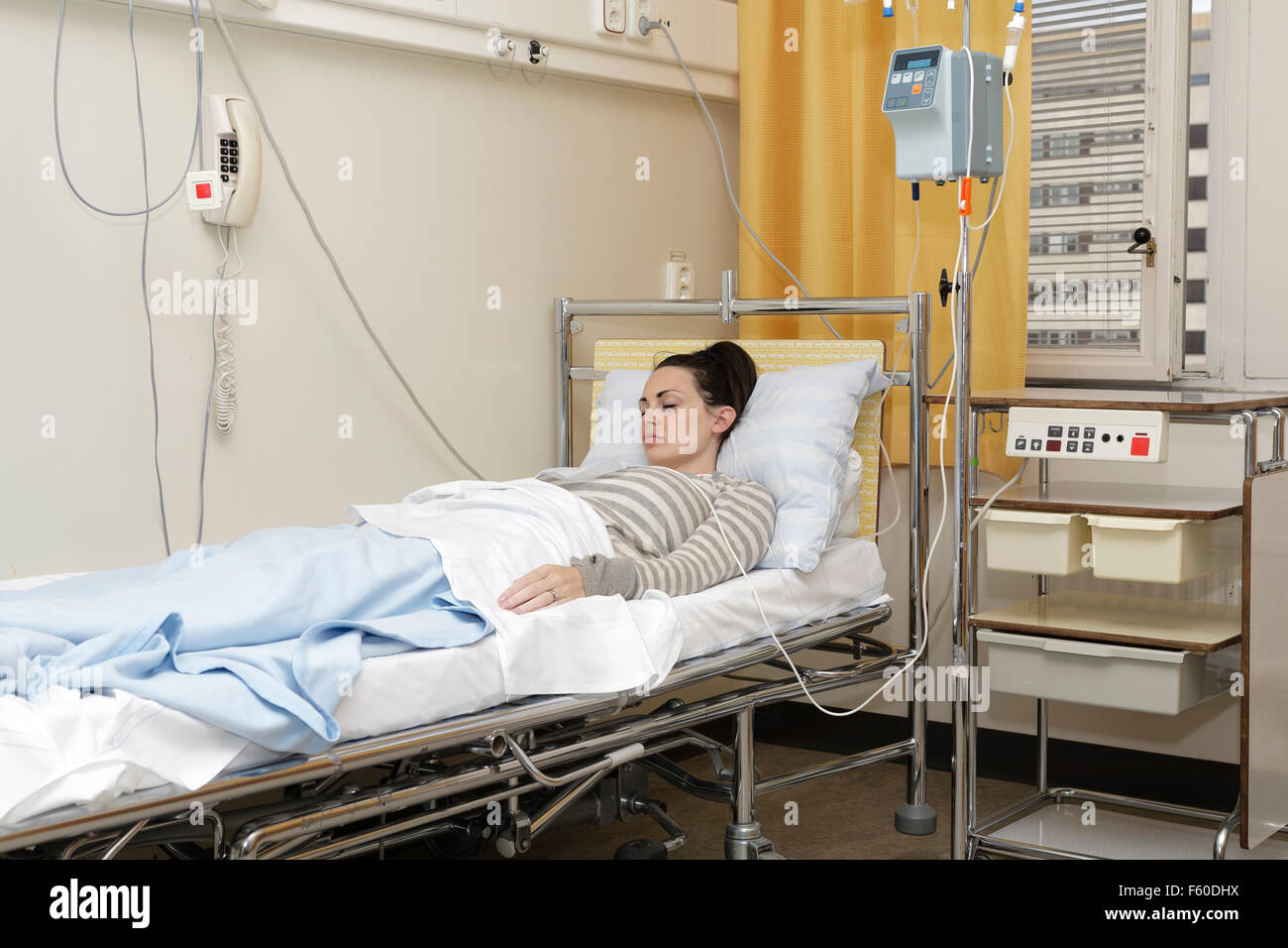 Sick young woman laying in hospital bed with Central Venous Catheter (CVC) being administered fluids and Parenteral - Stock Image