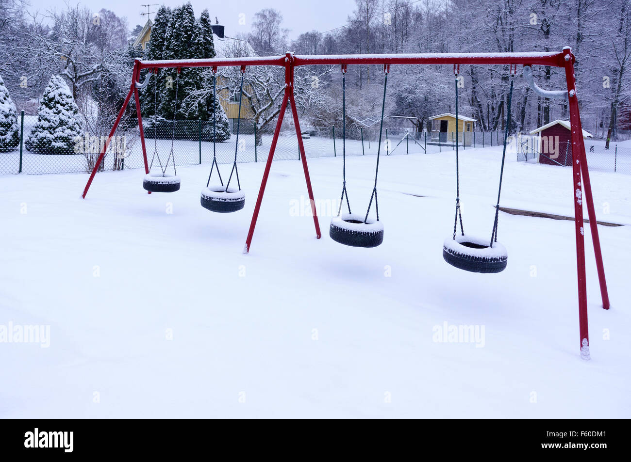 Kids outdoor playground swings covered in snow  Model Release: No.  Property Release: No. - Stock Image