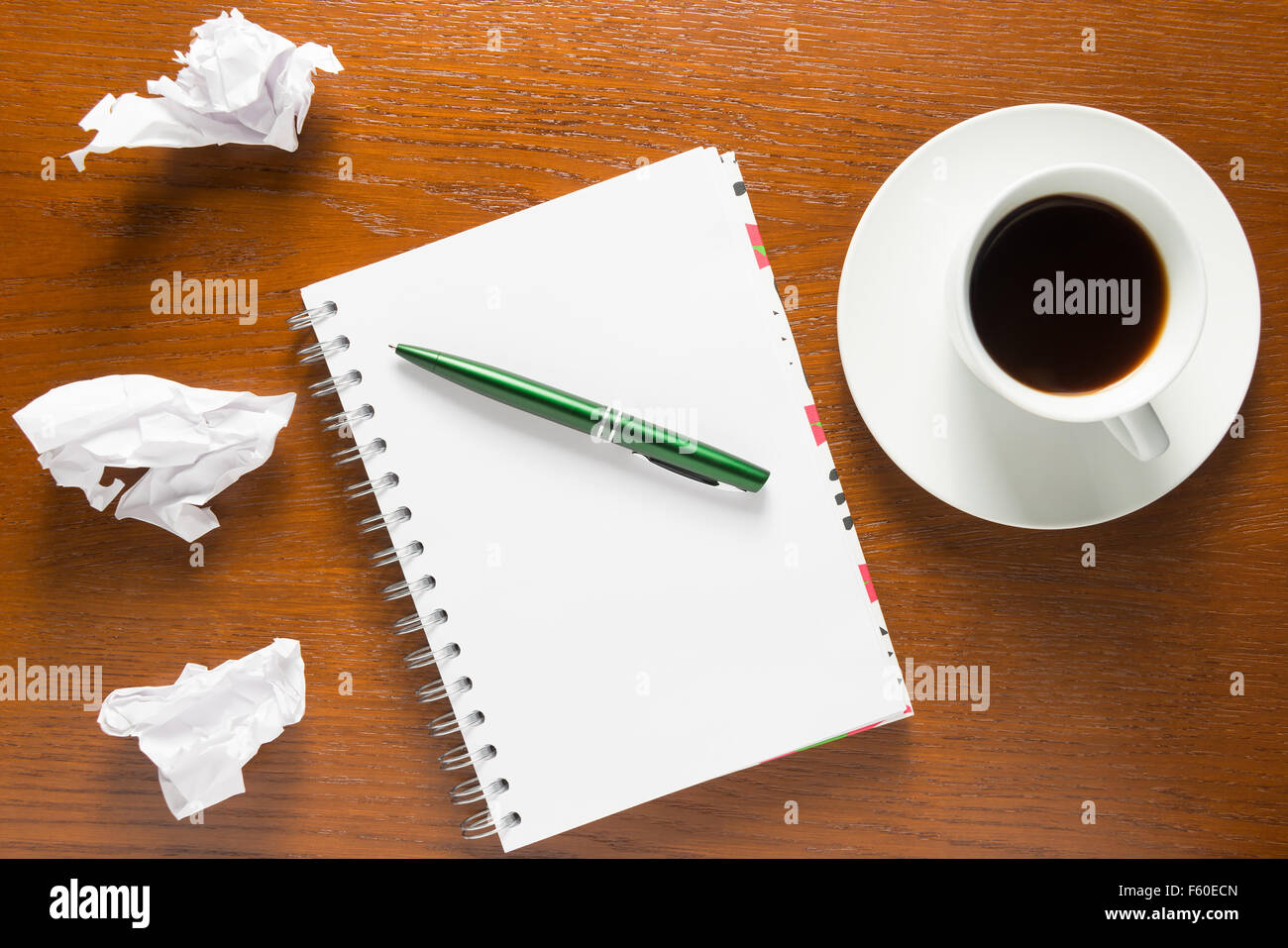 notebook and crumpled sheets of paper on top of view - Stock Image