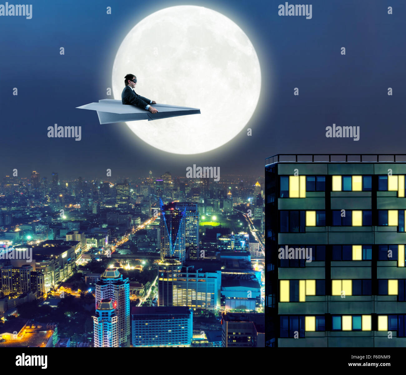 Businessman on paper airplane is flying above the city in the night - Stock Image
