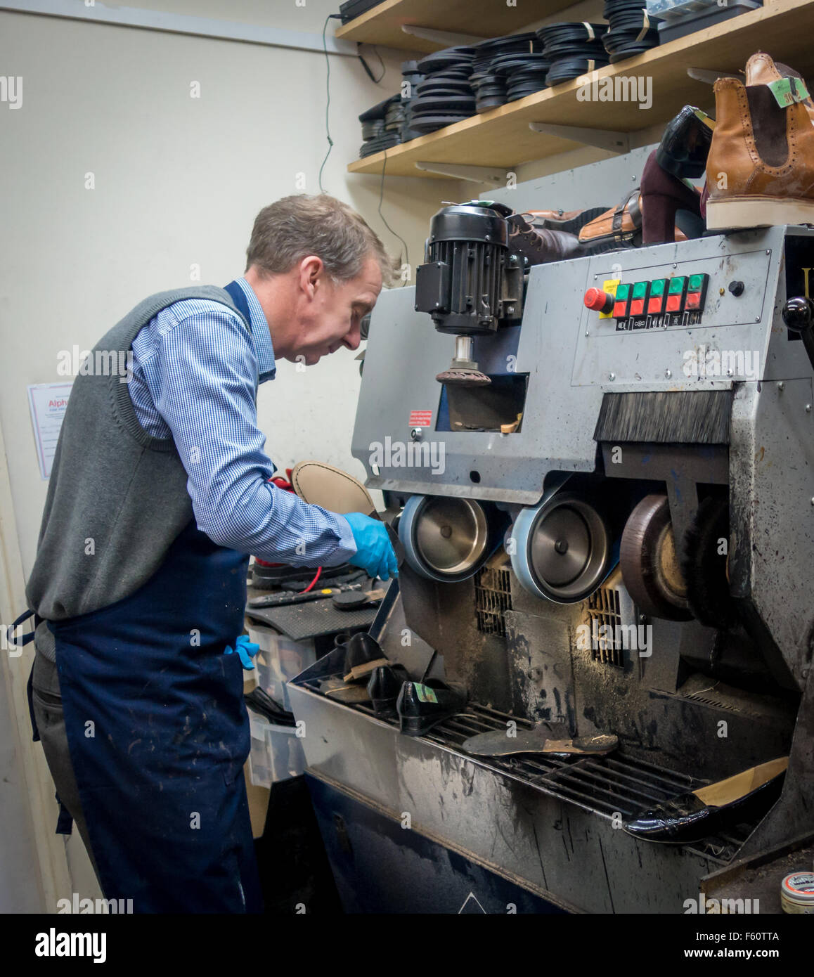 Man mending a pair of shoes at a machine Stock Photo