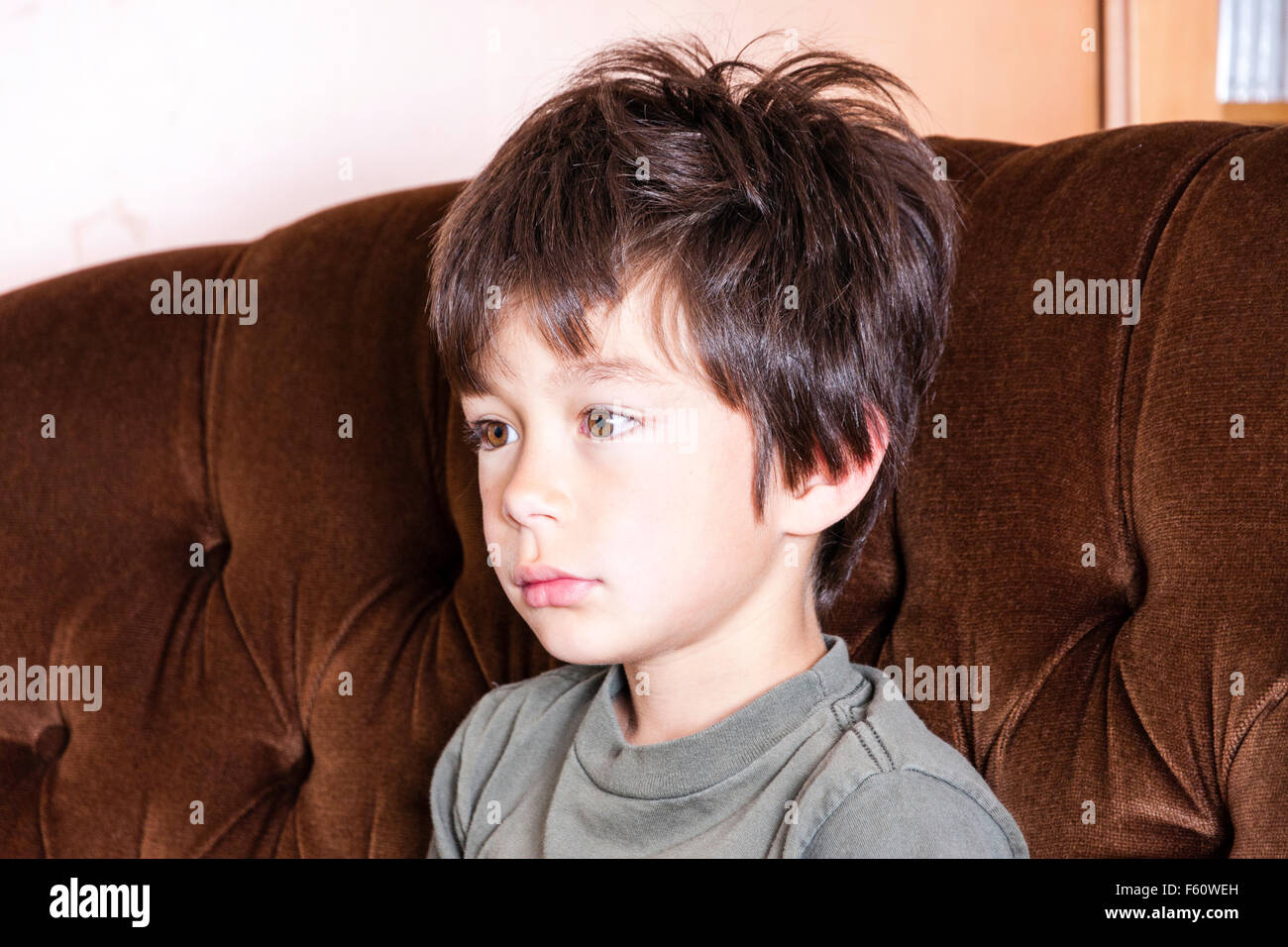 Brown haired Caucasian child, boy, 6-8 year old. Head shot, interior. Sitting on settee, sad lonely miserable expression, - Stock Image