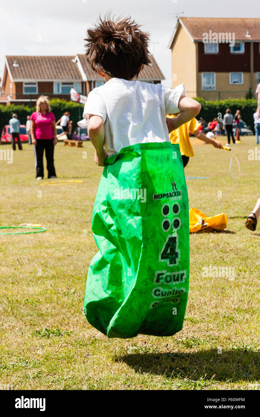 Child, Caucasian, boy, 7-9 years old. Exterior. School sports day. Sack race. Leaping holding sack with both hands. - Stock Image
