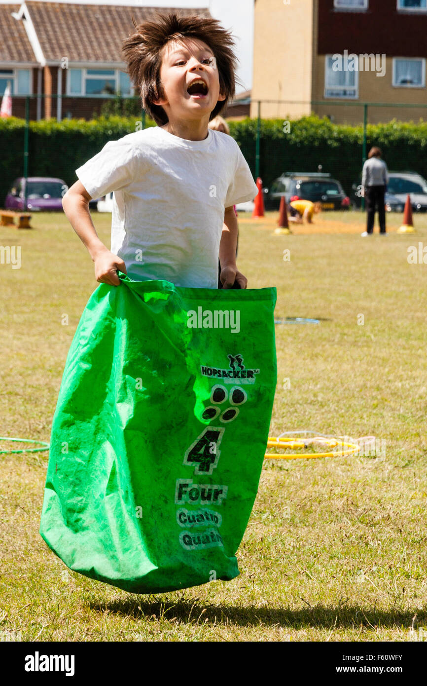 Child, Caucasian boy, 7-9 years old. Outdoors at school sports day. Sack race. Leaping holding sack with number - Stock Image