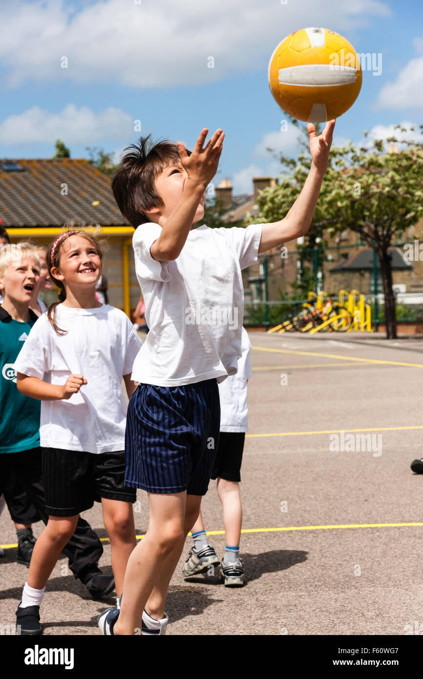 Child, Caucasian boy, 7-9 years old. Outdoors at School sports day. Jumping up and throwing basket ball into the - Stock Image
