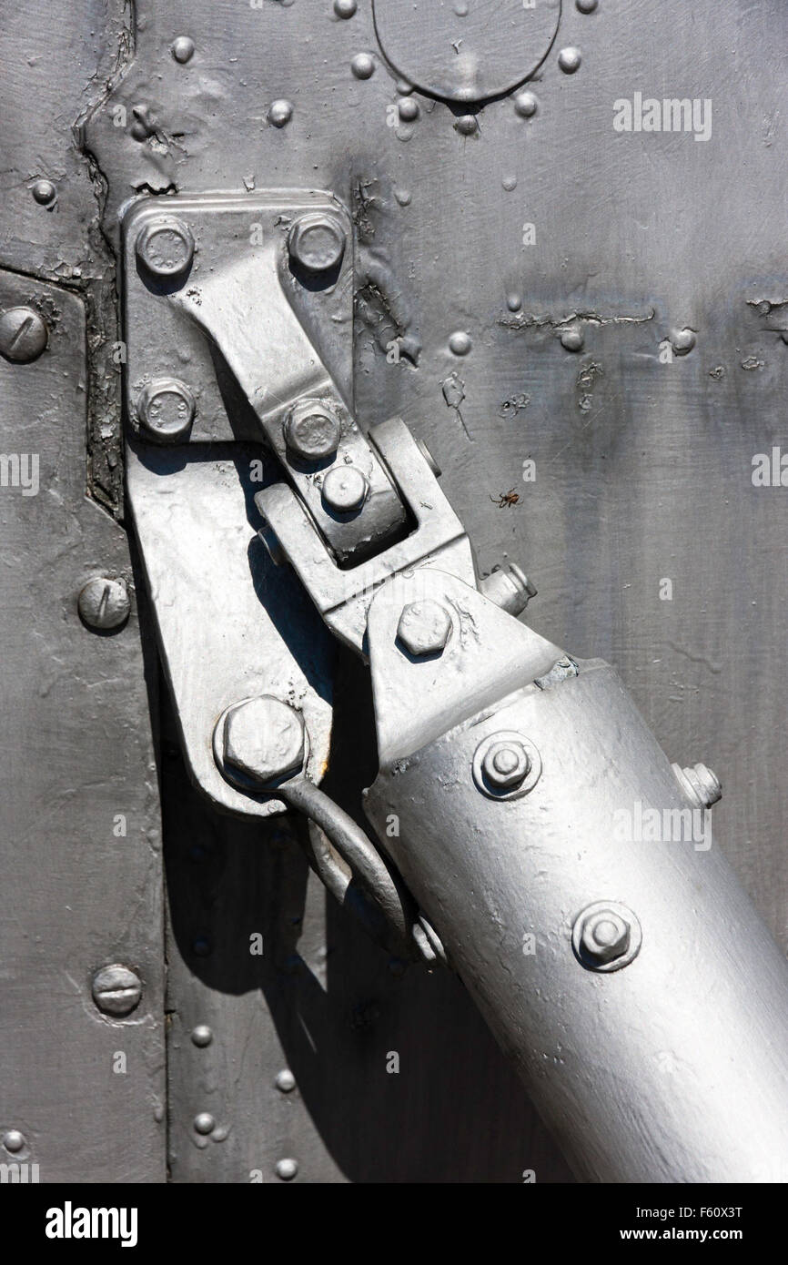 Metalwork. Strut attached to side of fuselage of airplane, showing bolted holding plate with links and joints. - Stock Image