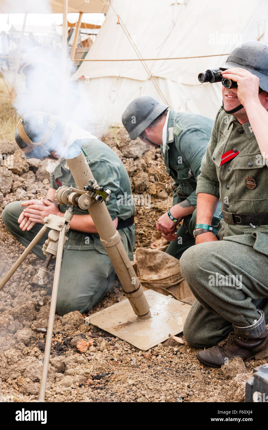 World war two re-enactment. German soldiers firing 8cm light trench mortar in dug out while officer looks through - Stock Image