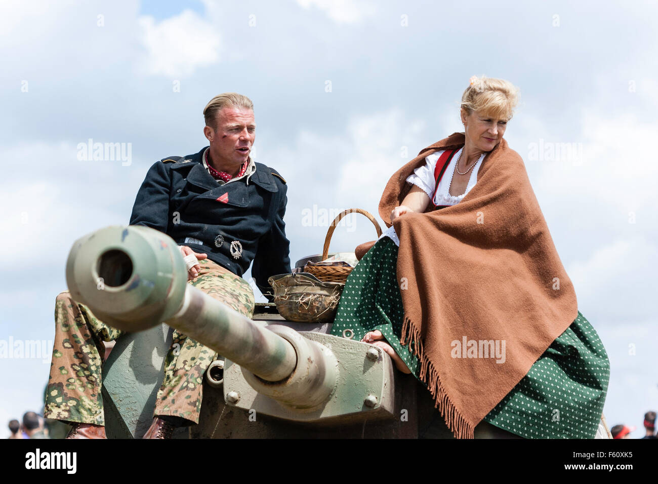 Second world war re-enactment. German panzer officer sitting on Tiger tank turret with woman in shawl in the sunshine, - Stock Image