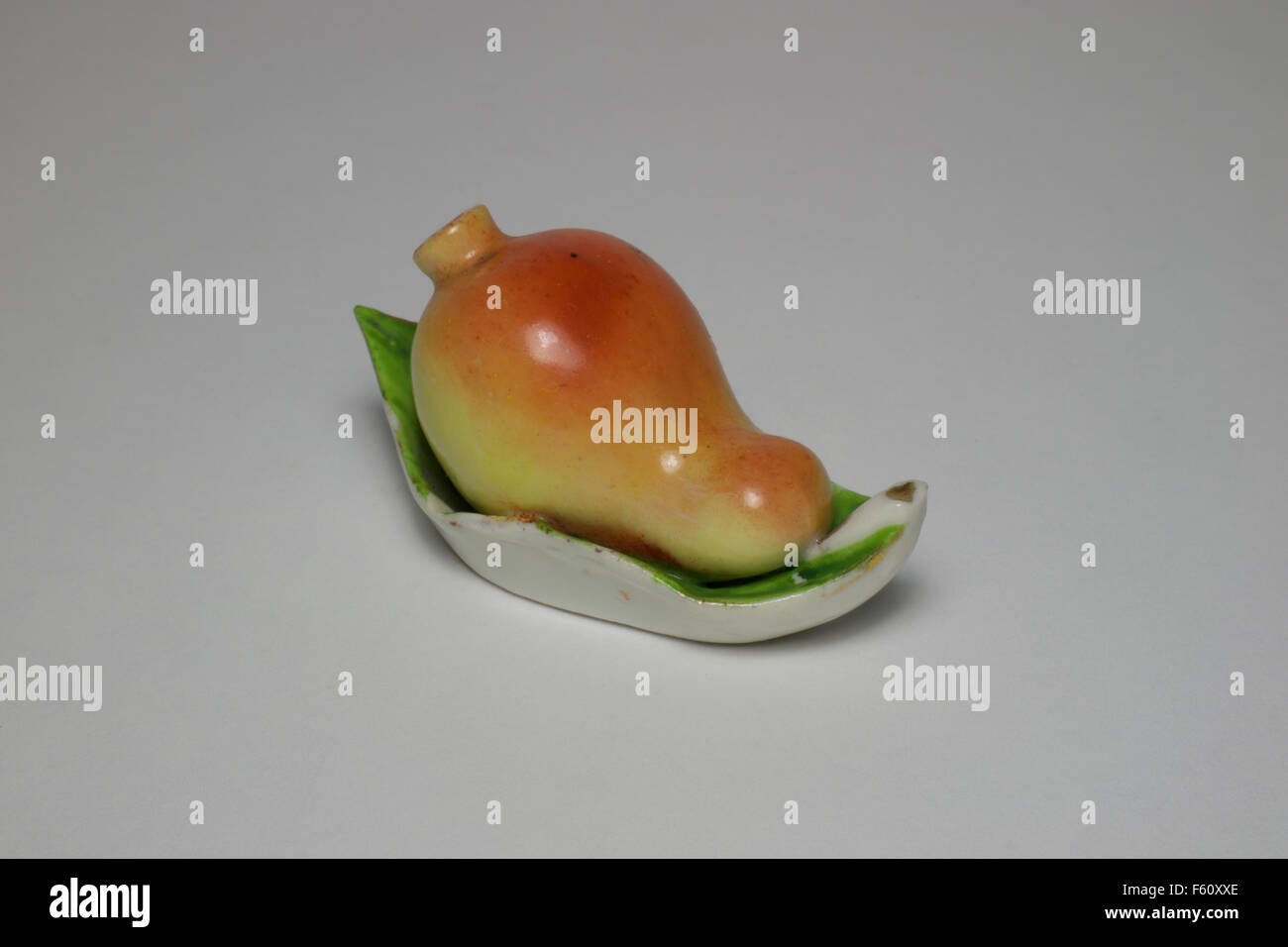 Porcelain perfume bottle in the form of a pear resting on a leaf. - Stock Image