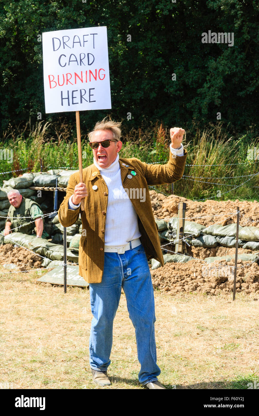 Vietnam War re-enactment. Lone Peace-movement protester standing and shouting with placard 'Draft card burning - Stock Image