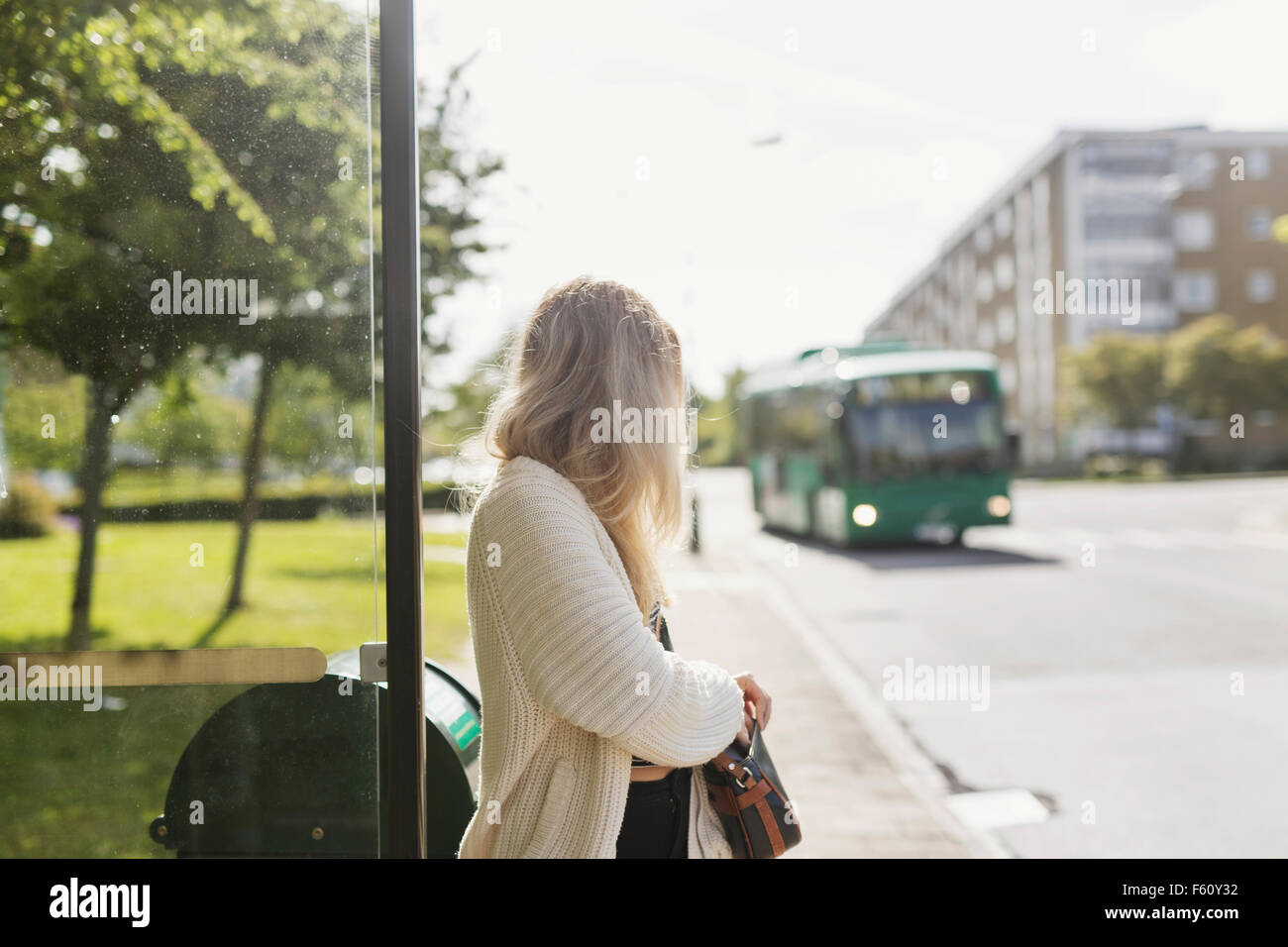 Young woman carrying shoulder bag standing near garbage bin looking at bus - Stock Image