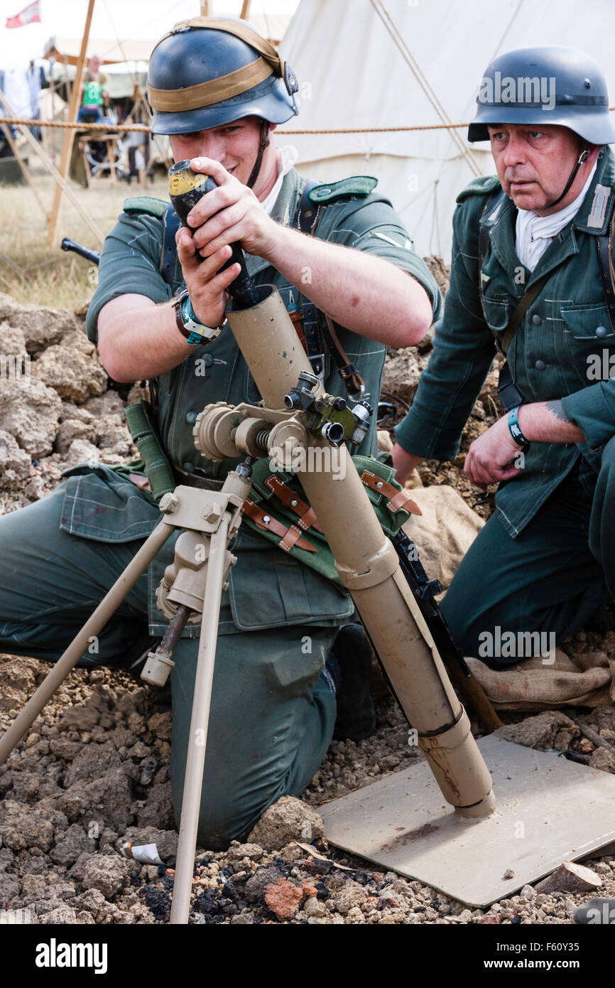 Second world war re-enactment. Two men mortar team in small dugout. one soldier loading 8 cm mortar shell into light - Stock Image