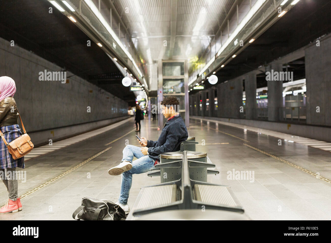Side view of man using smart phone while sitting on railroad station platform - Stock Image