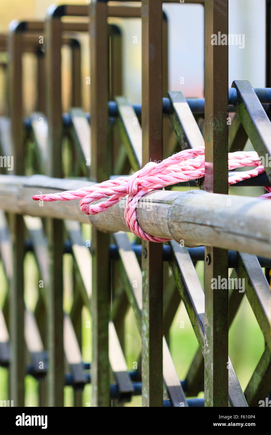 Japan, Kyoto, Arashiyama. Knot. Bamboo pole, tied to gate by red and white string to keep gate closed. Close-up. - Stock Image