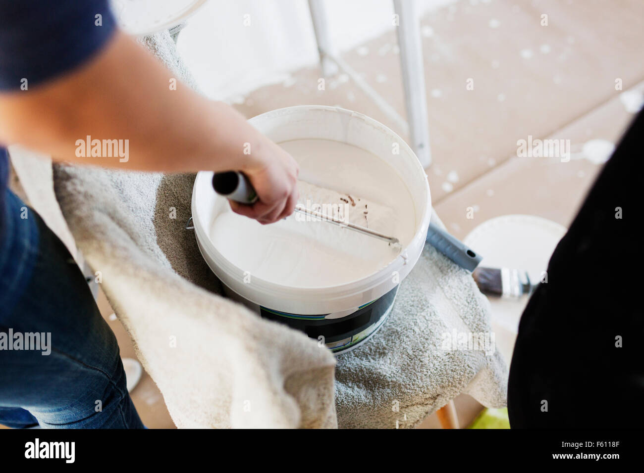Human hand dipping paint roller in paint container Stock Photo