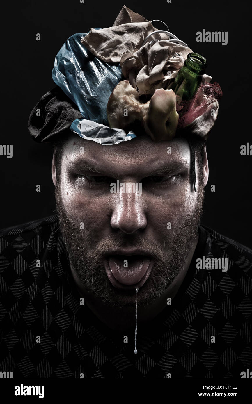 Ignorance concept. Heap of garbage inside silly man head - Stock Image