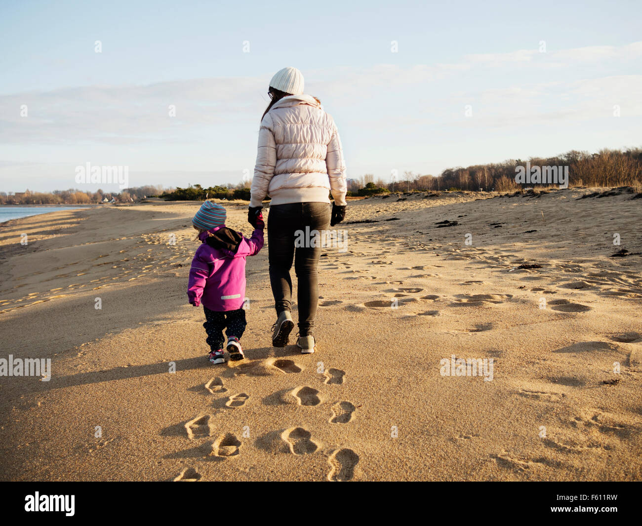Rear view of mother with daughter walking at beach - Stock Image