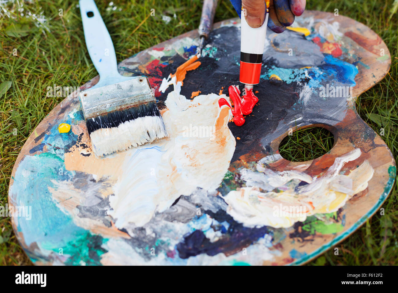 Cropped hand spilling red paint from tube on messy palette - Stock Image
