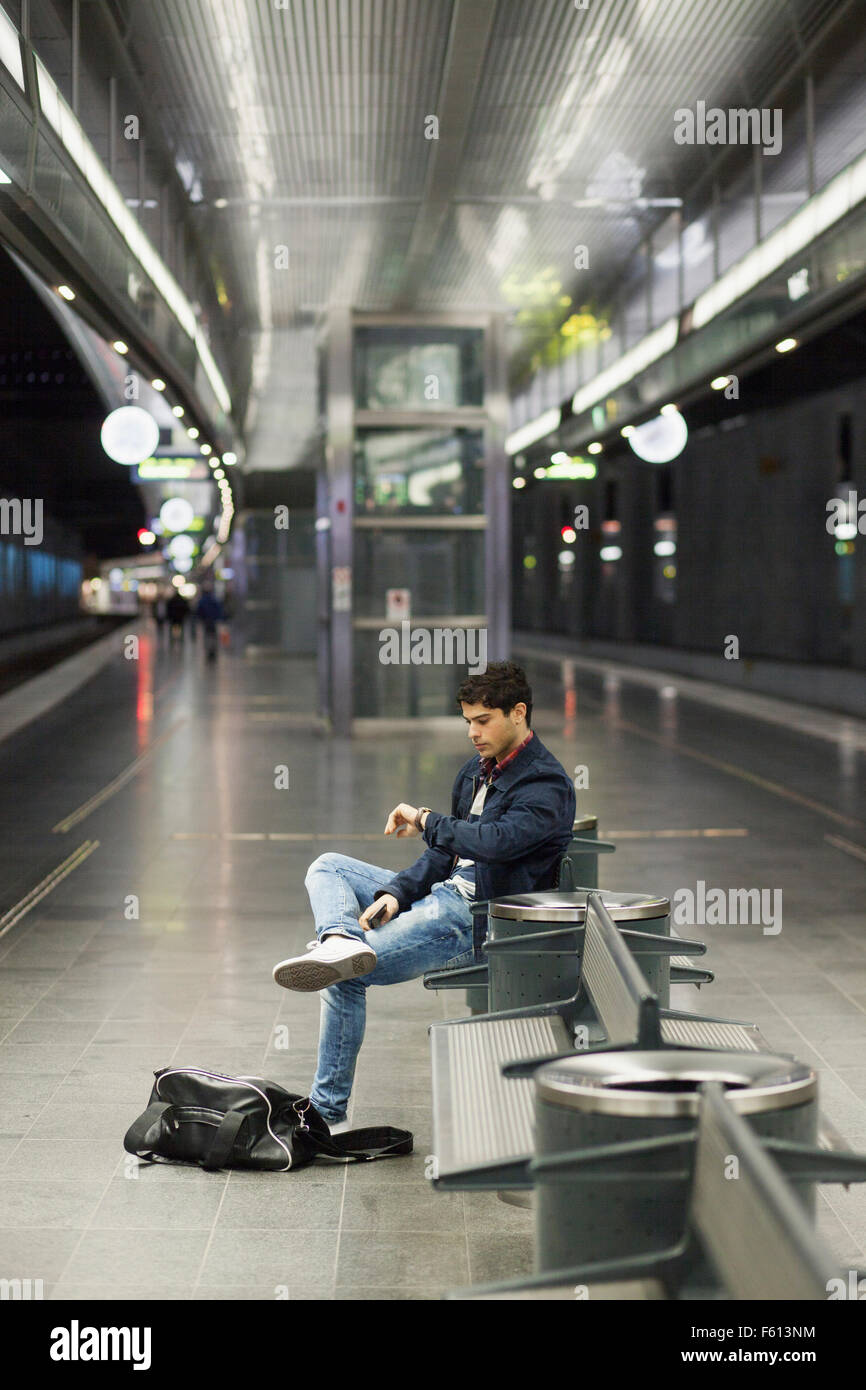 Man checking time while waiting at railroad station - Stock Image