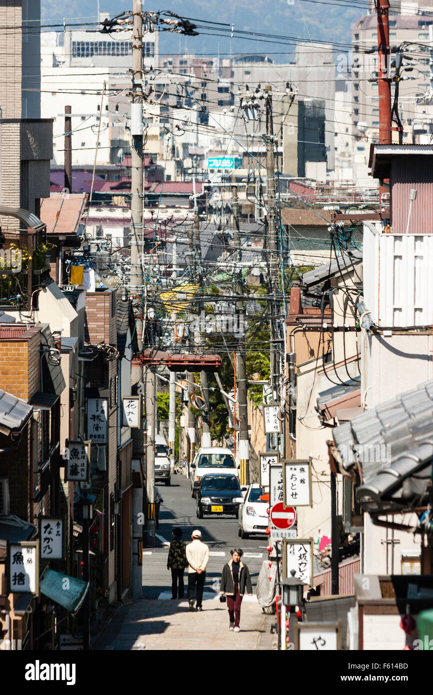 Japan, Kyoto. Telephoto view along typical Japanese long narrow shopping street sloping down to the city. People, - Stock Image