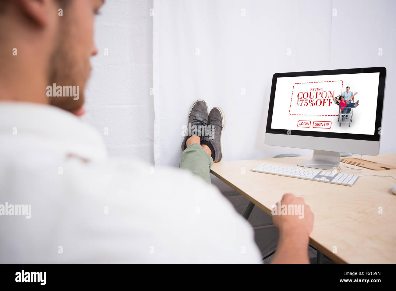 Composite image of businessman with legs crossed at ankle on office desk - Stock Image