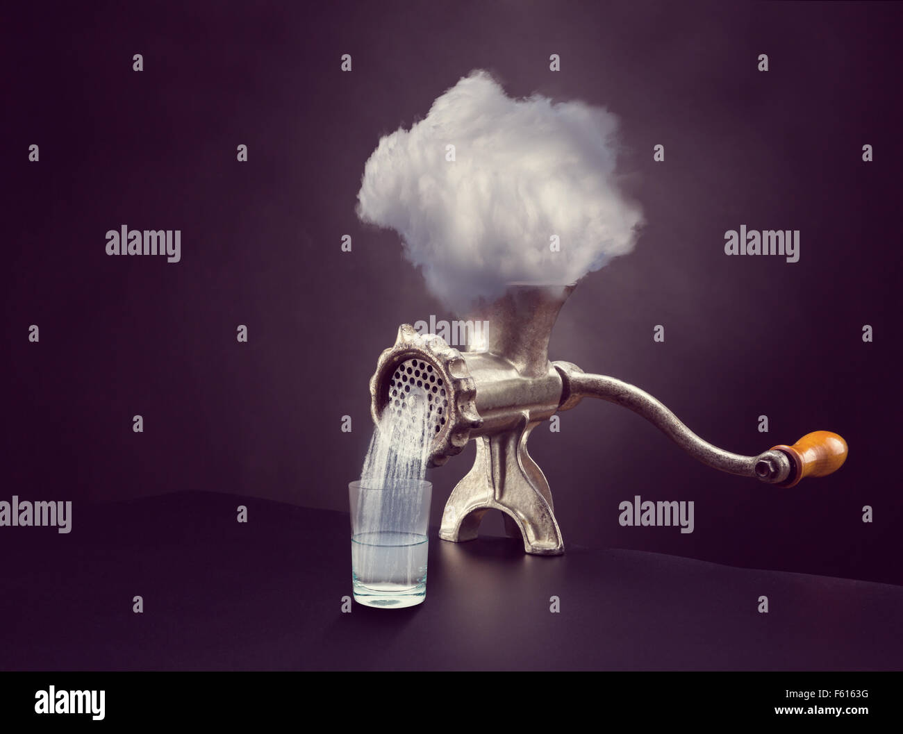 Cloud in the grinder over gray background - Stock Image