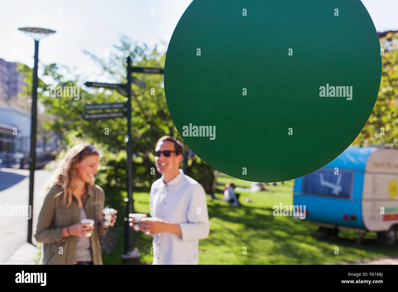 Happy couple holding disposable cups at park - Stock Image