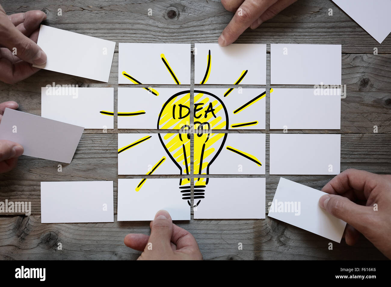 Business team brainstorming and finding a solution or good idea with light bulb drawing on business card paper - Stock Image
