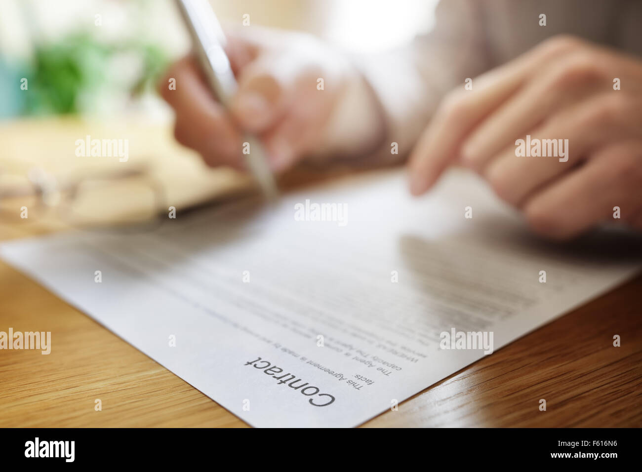 Businessman signing a legal contract document at his office desk - Stock Image