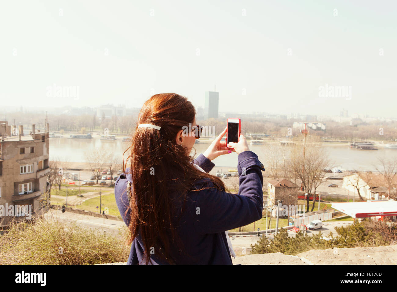 Rear view of young woman photographing cityscape against clear sky - Stock Image