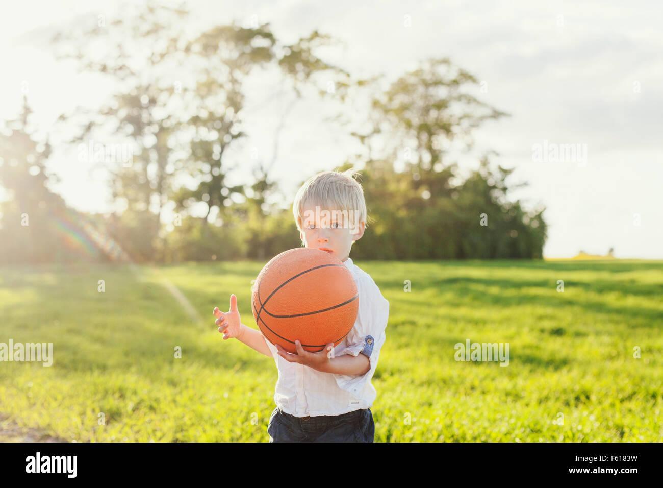 Portrait of cute boy holding basketball on field Stock Photo