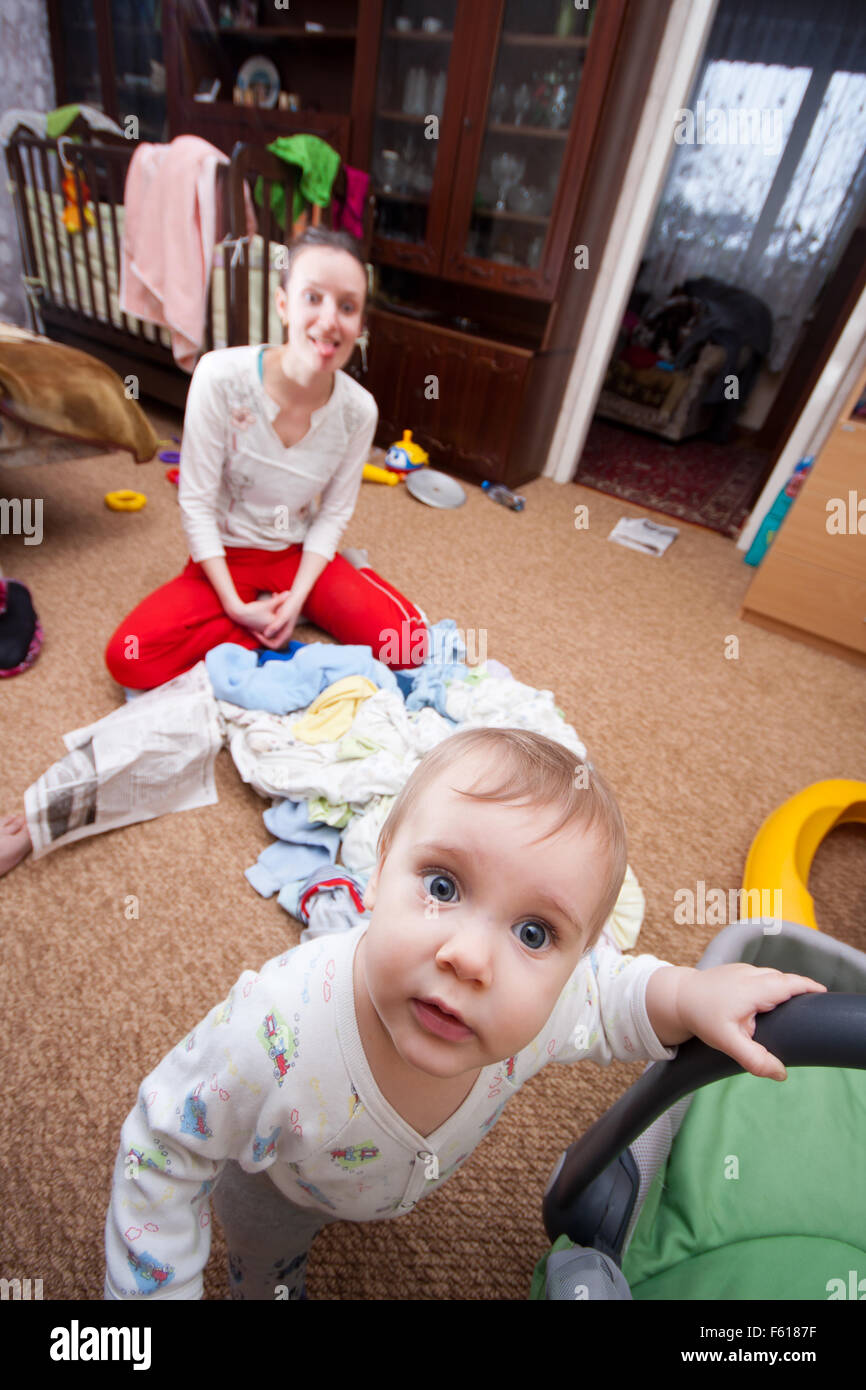 Scared baby escaping from crazy mother in mess interior - Stock Image