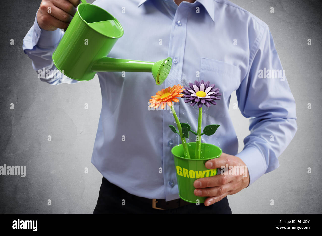 Investment and growth businessman with watering can investing in business and making money concept - Stock Image