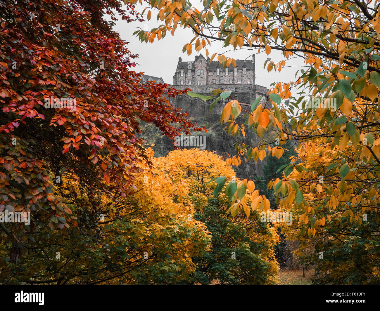 Edinburgh castle through the autumn trees in Princes Street Gardens. - Stock Image