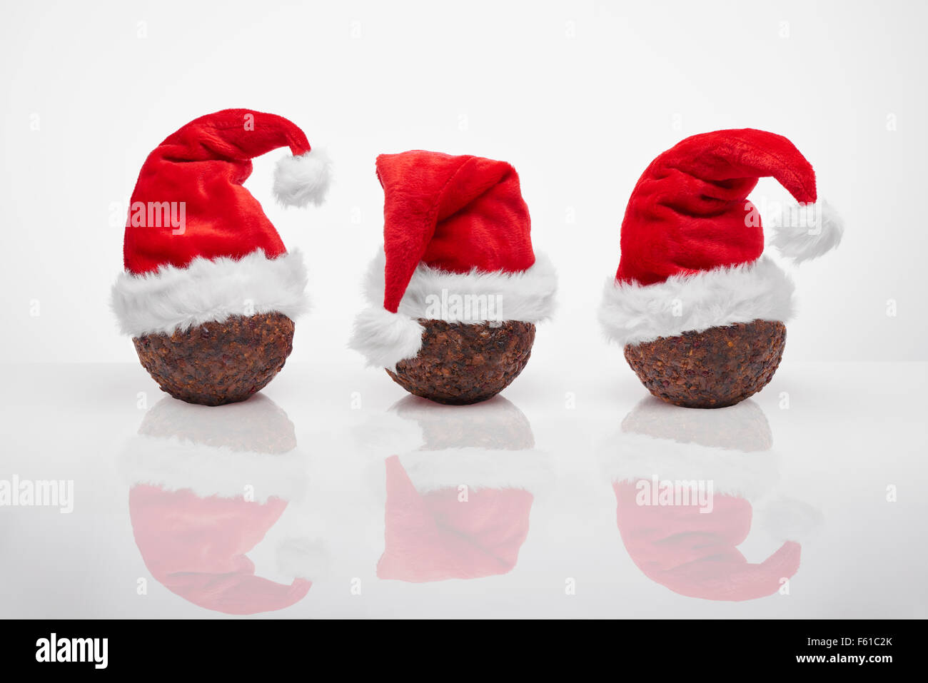 Christmas Puddings with red Santa hats - Stock Image
