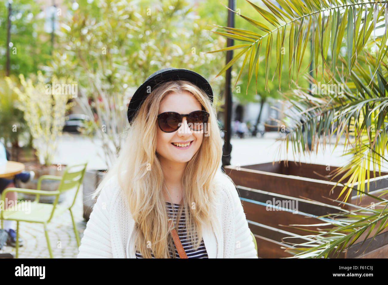 Beautiful smiling young woman sitting at cafe - Stock Image