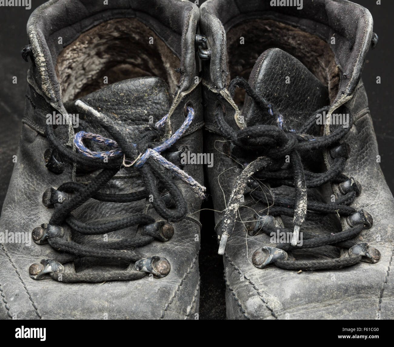 Old black worn out shoes closeup - Stock Image