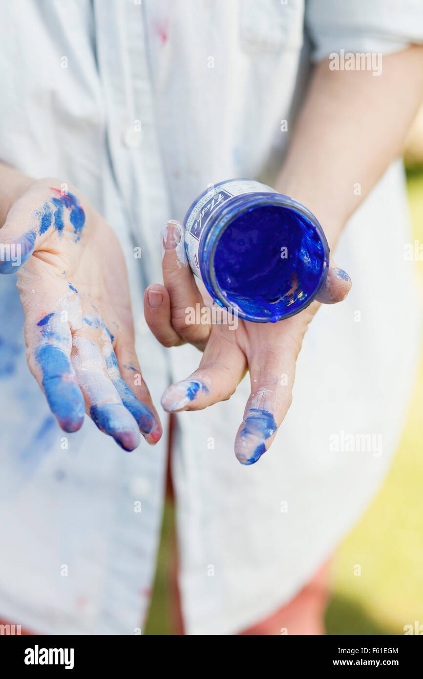Midsection of senior female painter with messy hands holding blue paint can outdoors - Stock Image