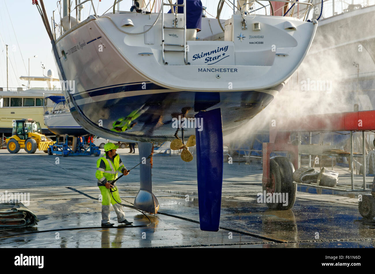 Cruising yacht being lifted and jet-washed to remove marine fouling. - Stock Image